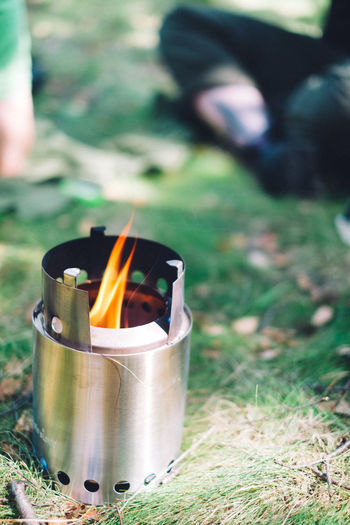 Camping Hiking Burning Camping Camping Stove Container Day Field Fire Fire - Natural Phenomenon Flame Focus On Foreground Food And Drink Glowing Grass Heat - Temperature Land Nature Outdoor Cooking Outdoors People Plant Real People Selective Focus