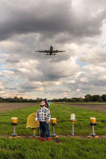 Full length of boy looking up with airplane flying over grass against sky