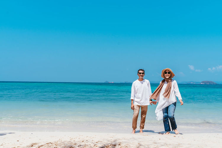 Portrait of couple standing at beach