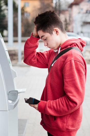 Side view of young man standing by atm machine