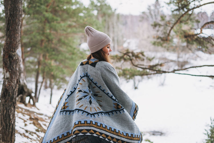 Young brunette beautiful woman in hat and grey poncho walking in the winter forest