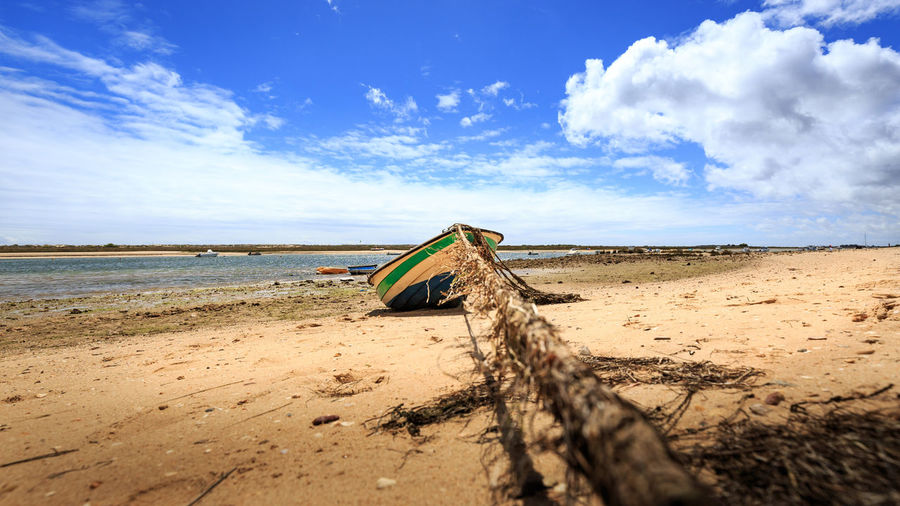 Fishing boat moored at beach against cloudy sky
