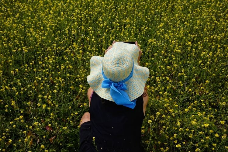 High angle view of woman photographing while crouching at rape field