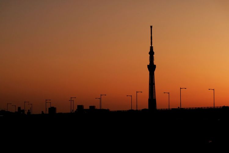 Silhouette Of Communication Tower With Street Lights And Vehicles At Dusk