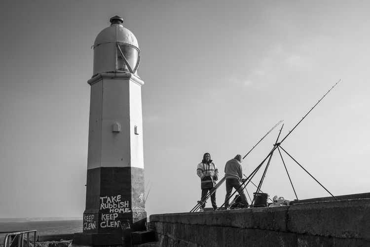 Lighthouse Low Angle View Porthcawl South Wales Architecture Built Structure Coastal Activity Day Fisherman Fishing Human Representation Leisure Activity Low Angle View Men Monochrome Occupation Outdoors Pastime People Real People Sculpture Sky Statue Working