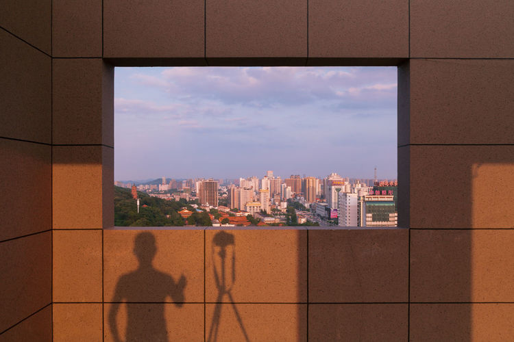 Shadow Of Man With Tripod On Wall In Building
