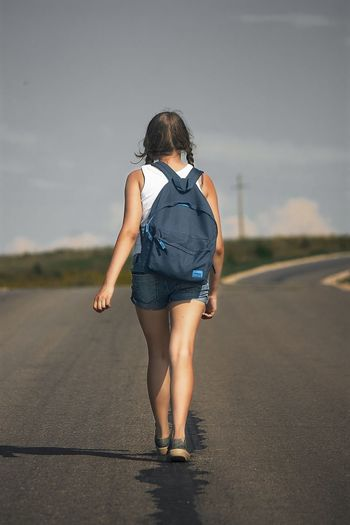 Rear View Of Young Woman With Backpack Walking On Road