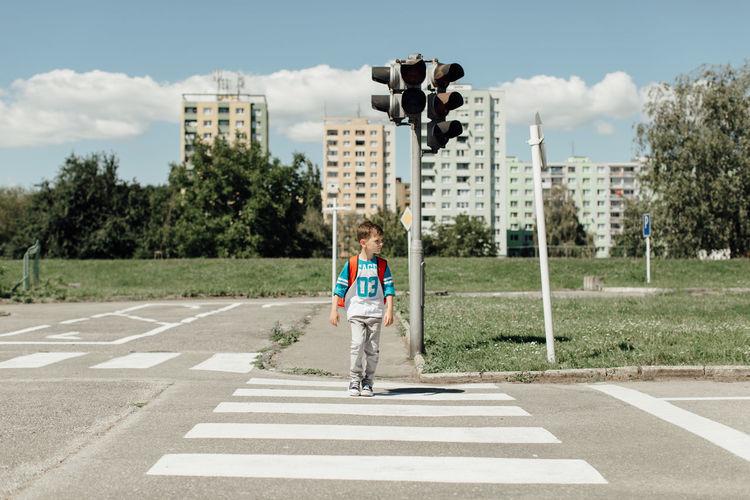 Schoolboy crossing a road on his morning way to school. 6 Years Copy Space Horizontal Traficlight Walk Back To School Caucasian Child Clouds And Sky Crossing Day Full Length Kid Look Left Look Right One Person Pedestrian Real People Road Safety School Traffic Lights Trafic Sign Walking Zebra Crossing