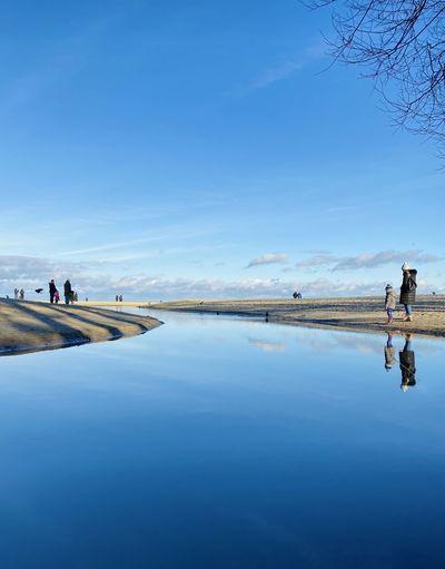 People on water against blue sky
