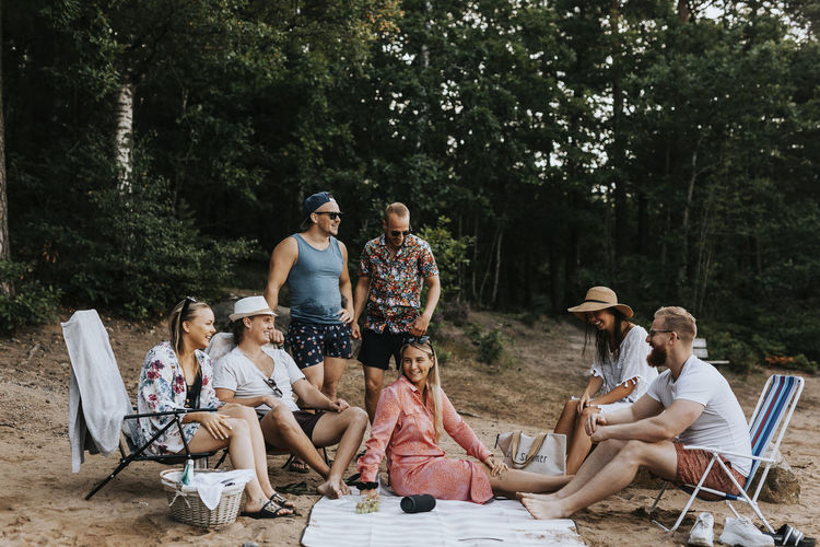 People sitting on grassland against trees