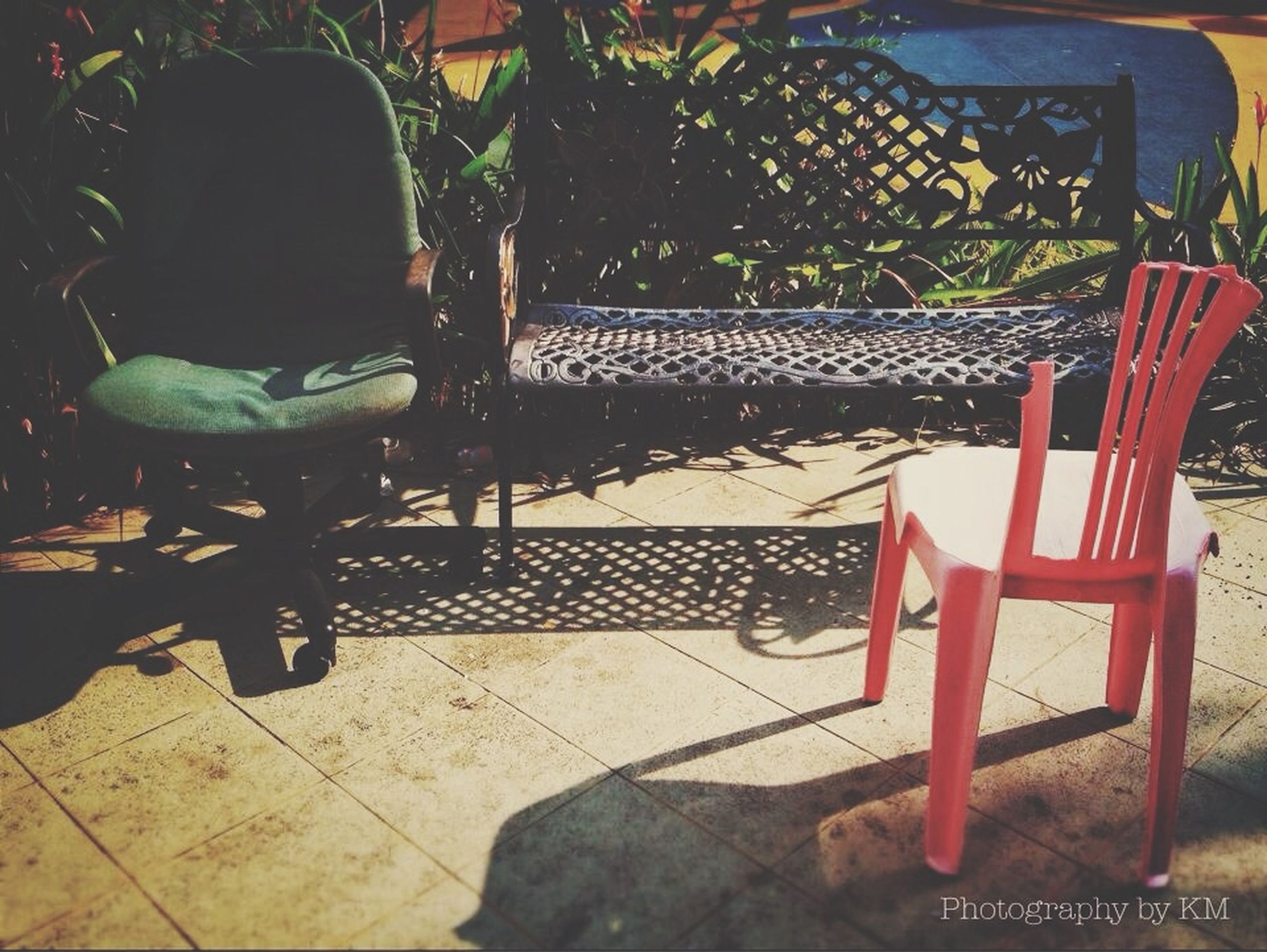 chair, table, potted plant, seat, absence, empty, plant, bench, furniture, sunlight, restaurant, day, relaxation, sidewalk cafe, high angle view, front or back yard, growth, outdoors, shadow, no people