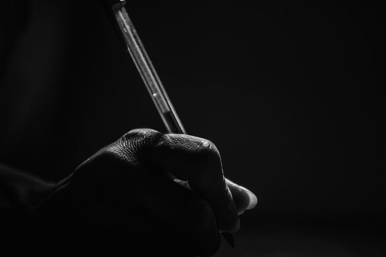 Close-up of hand holding cigarette against black background