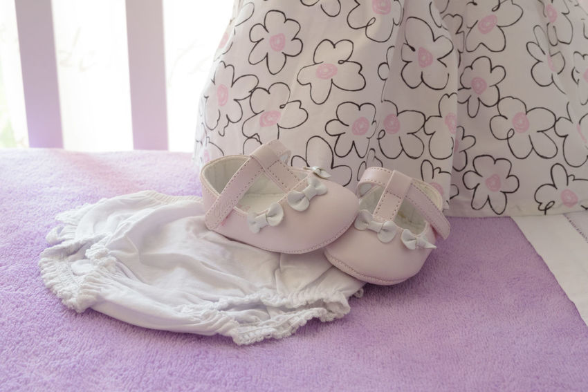 Bay girl clothes for christening day Baby Dress Babygirl Bed Childhood Christening Day Close-up Communication Emotion Floral Pattern Pink Color Purple Relaxation Still Life Textile White Color
