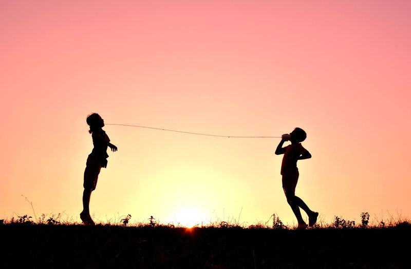 Silhouette of two people jumping against sky at sunset