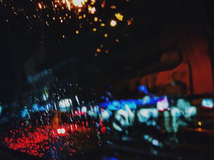Defocused image of illuminated city seen through wet window
