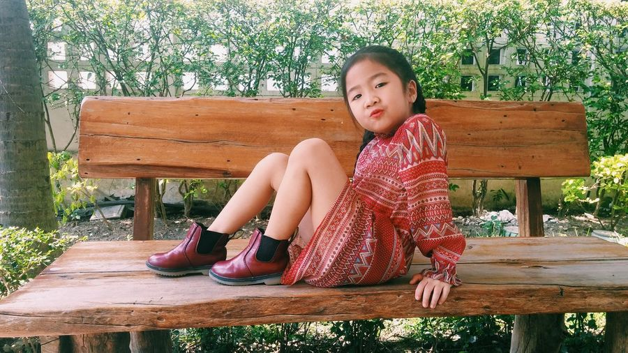 Portrait of girl puckering lips while sitting on wooden bench at park