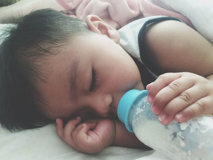 Close-up of baby boy drinking milk on bed at home