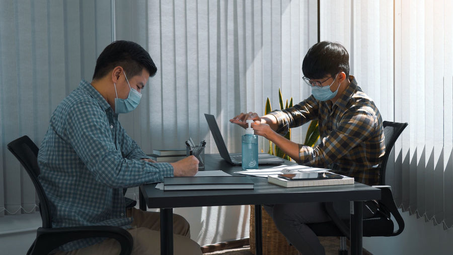 Business persons wearing mask sitting at office