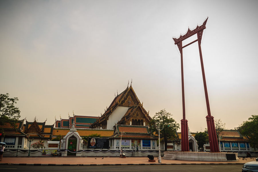 Vintage view of the Giant Swing, a religious structure which located in front of Wat Suthat temple. It was used in the Brahmin ceremony and is one of Bangkok famous tourist attraction. Crowd Of Pigeon Giant Swing Giant Swing Bangkok Red Giant Swing Sao Ching Cha Tourist Attraction  Wat Suthat Wat Suthat Thepwararam Architecture Belief Building Building Exterior Built Structure Car City Day Mode Of Transportation Motor Vehicle Nature No People Outdoors Place Of Worship Religion Sky Spirituality Sunset Tourist Attraction In Thailand Tourist Attractions Tourist Attractions, Tourist Destinations, City Life, Leisure Activities, Transportation