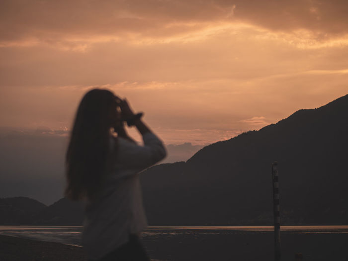 Woman photographing against sky during sunset