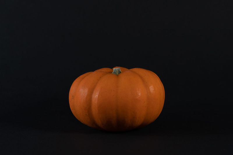 Close-up of pumpkin against black background. isolated, concept for clock change and harvest time.