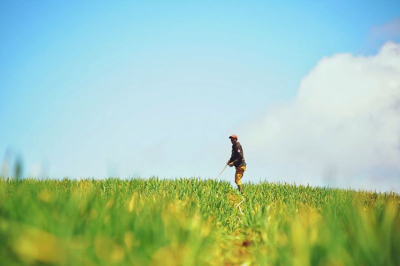 Side view of farmer standing on agricultural field against sky
