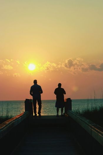 Rear view of silhouette men standing on pier during sunset