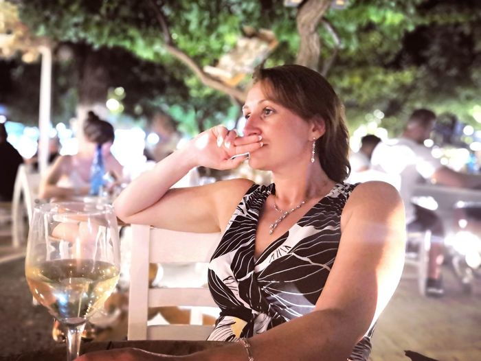 Thoughtful woman having wine at outdoor restaurant during night