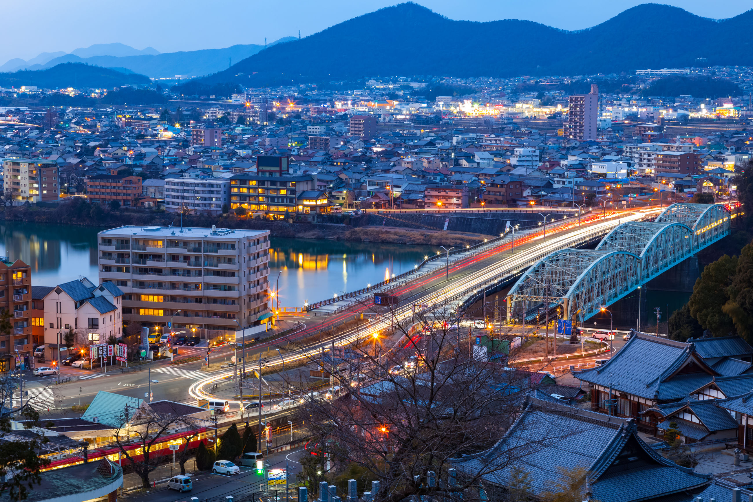 architecture, cityscape, city, built structure, illuminated, building exterior, high angle view, crowded, night, transportation, bridge - man made structure, river, connection, mountain, aerial view, city life, residential district, bridge, residential building, travel destinations