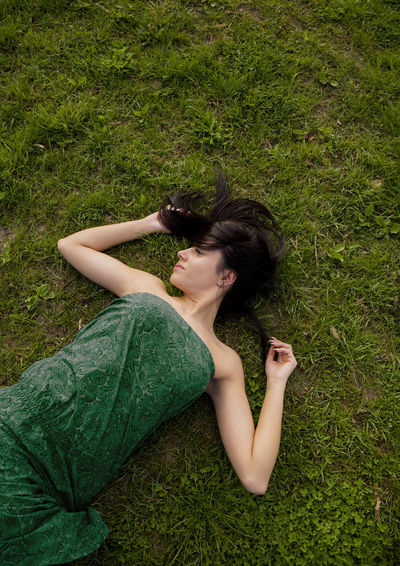 High Angle View Of Young Woman Relaxing On Field