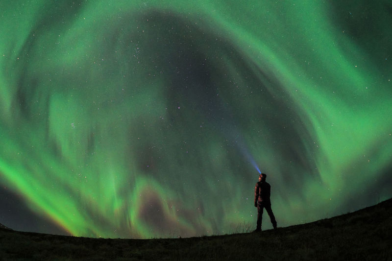 Low angle view of man using flashlight towards aurora borealis in sky