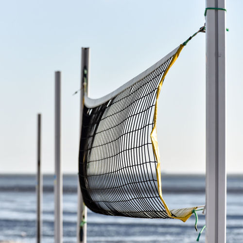 Close-up of net at beach against sky
