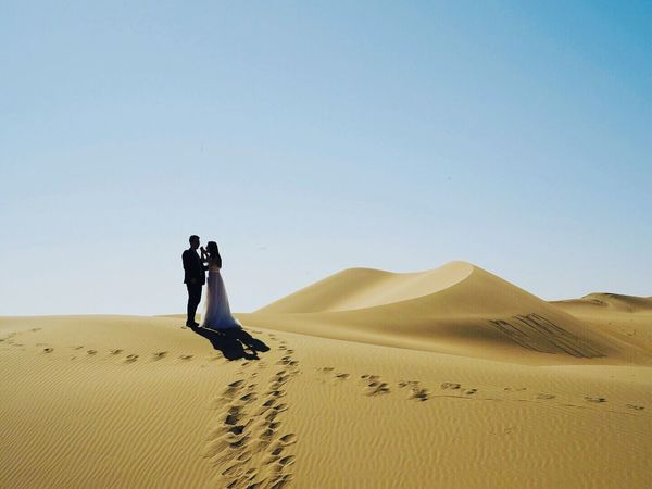 CrossroadBride Sand Desert Sand Dune Arid Climate Clear Sky Landscape Nature Extreme Terrain Remote Full Length Outdoors Day Copy Space Scenics Beauty In Nature Tranquil Scene Two People Tranquility Real People Sky Lost In The Landscape Connected By Travel