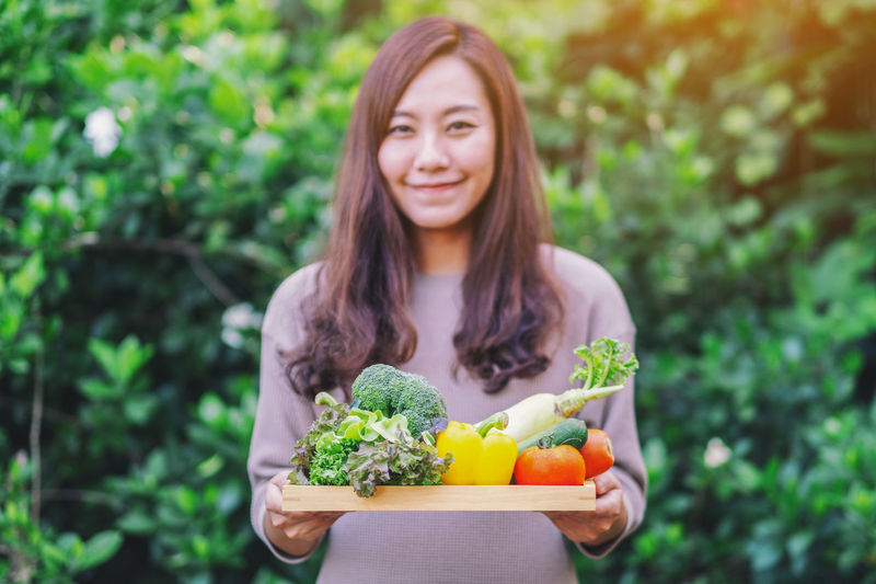 Portrait of smiling woman holding food against plants