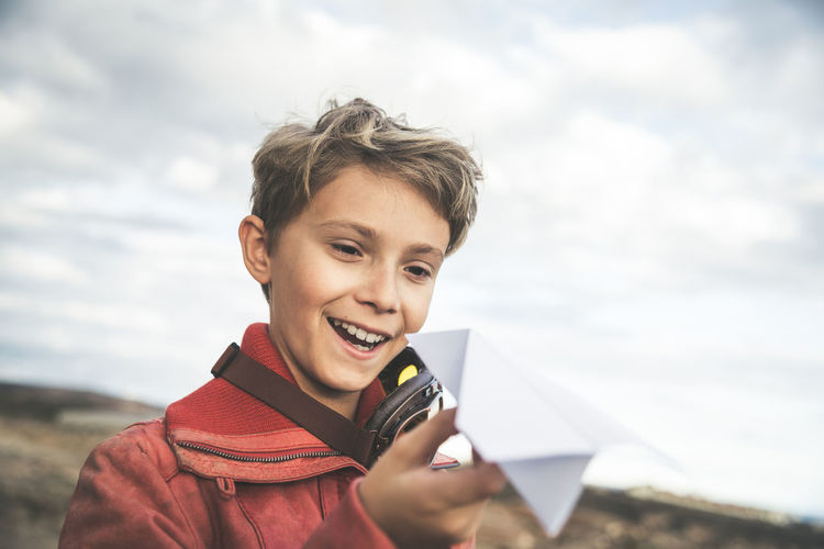 Portrait of smiling boy holding camera against sky