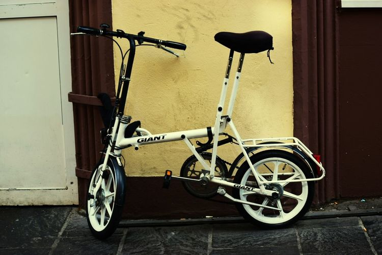 Bicycle Transportation Mode Of Transport Stationary Land Vehicle Wheel Tire Cycling Wall - Building Feature Parking Retro Styled Pedal Travel Exercise Bike No People Business Finance And Industry Old-fashioned Day Vehicle Seat Outdoors Small Giant