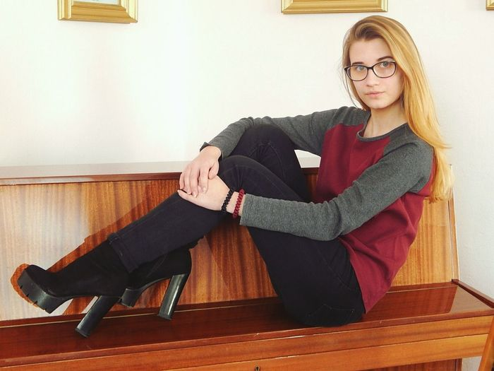 Full length portrait of young woman sitting on wooden bench