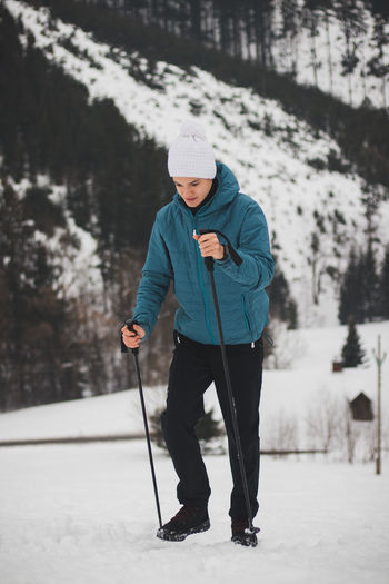 Teenager in a white cap with a pompom and a blue jacket climbs a mountain using trekking poles