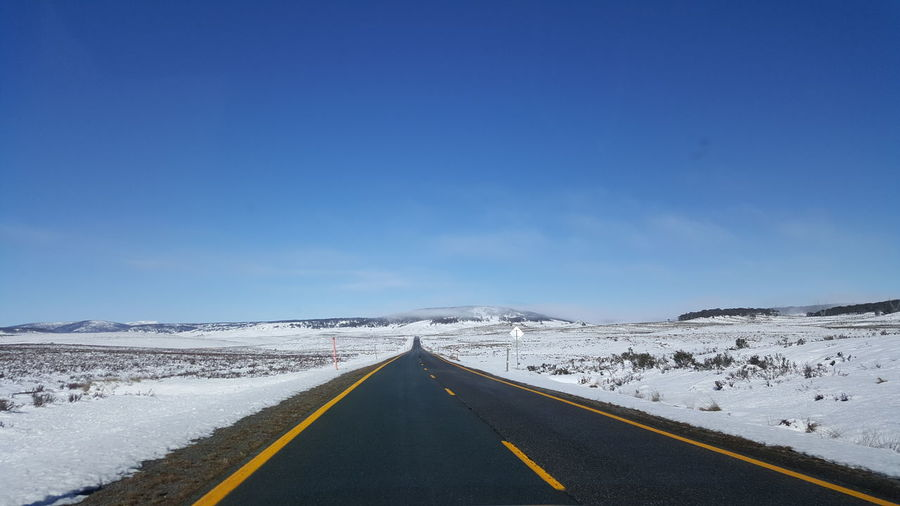 Empty road against blue sky during winter
