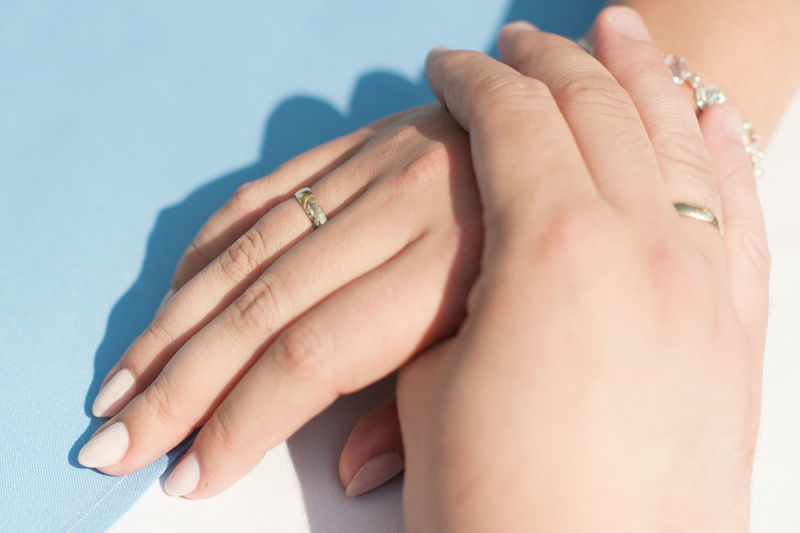 High angle view of hands wearing rings at table