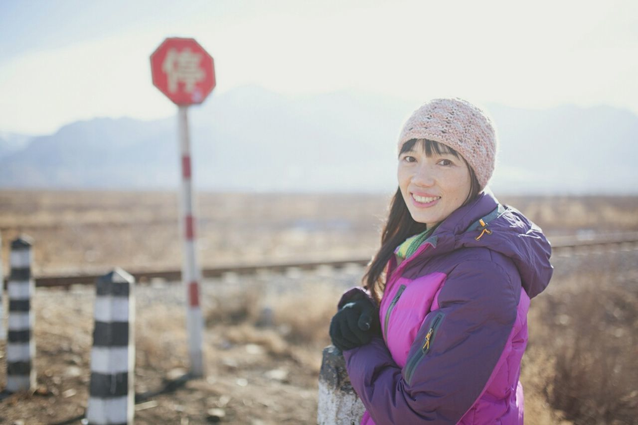 smiling, one person, looking at camera, real people, portrait, leisure activity, lifestyles, mountain, standing, happiness, day, outdoors, focus on foreground, nature, vacations, young women, warm clothing, cold temperature, young adult, beauty in nature, sky, adult, people