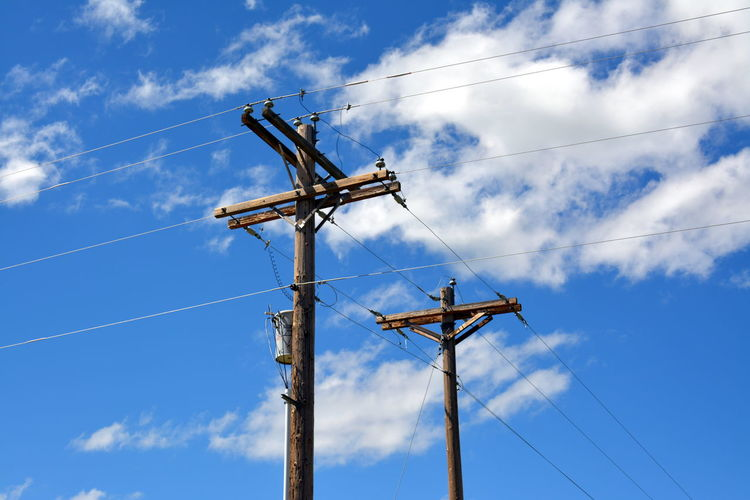 Low section of electric poles against sky