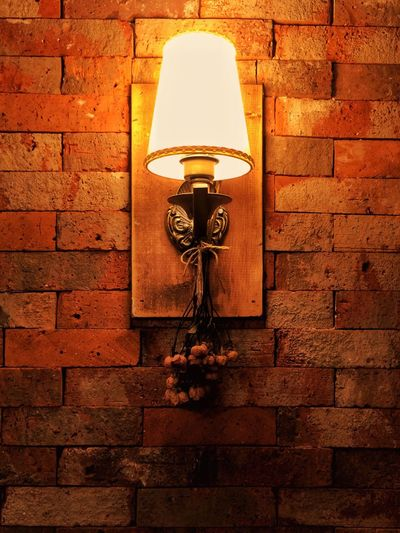 Low angle view of illuminated lamp hanging against brick wall