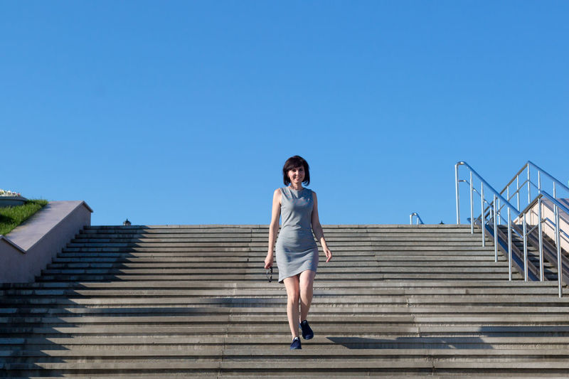 Low angle view of woman standing on staircase against blue sky