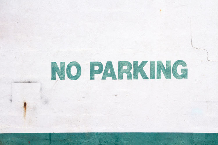 Close-up of no parking sign on white wall