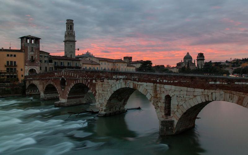 View of ponte pietra bridge at sunset