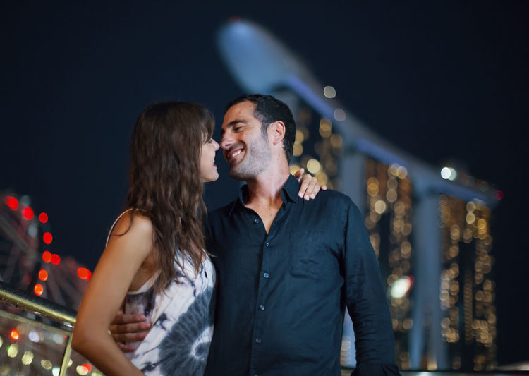 Man and woman at illuminated park at night