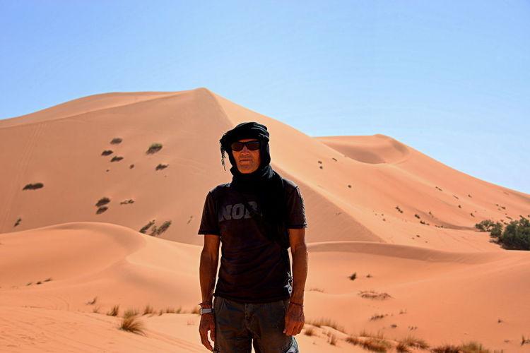 Man standing on sand dune in desert against clear sky