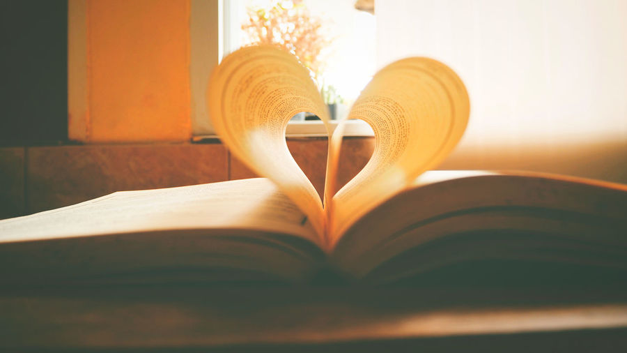 A book is opening on desk in a summer Book Close-up Day Education Heart Shape Indoors  Knowledge Literature Love No People Open Page Paper Still Life Sunlight Table Wisdom
