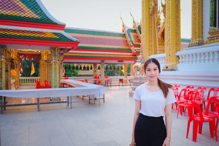 Portrait of young woman standing at temple